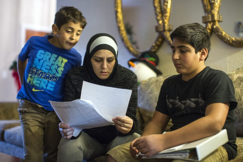 "Six days after the San Bernardino shooting, 14-year-old Hassan Messelmani (R) was told by a teacher to ""quit acting like a terrorist."" He's shown here with his mother Samira Elzayat and 6-year-old brother Rami. (Maya Sugarman/KPCC)"
