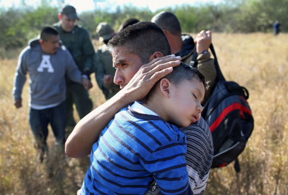 A father holds his sleeping son, 3, after they and other undocumented immigrants were detained by Border Patrol agents on December 7, 2015 near Rio Grande City, Texas. (John Moore/Getty Images)