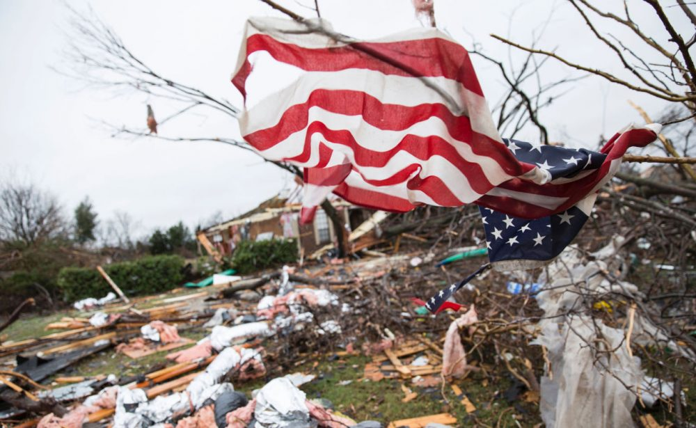 An American flag placed by first responders is seen December 27 in the aftermath of a tornado in Rowlett, Texas. At least 11 people lost their lives as tornadoes tore through Texas, authorities said, as they searched home to home for possible more victims of the freak storms lashing the southern United States. Laura Buckman/AFP/Getty Images)