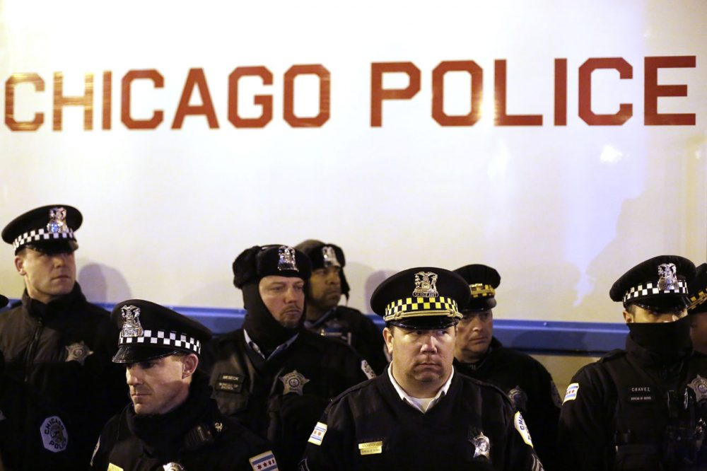 Chicago police officers surround a police vehicle as they watch demonstrators protesting the fatal police shooting of Laquan McDonald December 18 in Chicago, Illinois. (Joshua Lott/Getty Images)