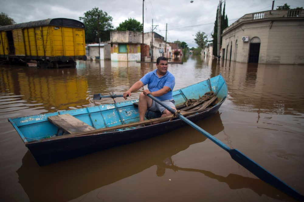 "A local rows his boat through a flooded street in Concordia, Entre Rios province, Argentina, on December 29. Over recent days the storms blamed on the ""El Niño"" weather phenomenon have killed four people in Brazil and two in Argentina. (STR/AFP/Getty Images)"