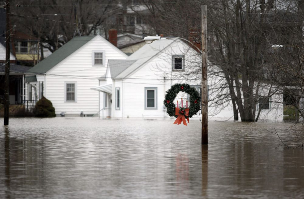 A holiday wreath hangs from a light post surrounded by floodwater from the Bourbeuse River, Tuesday, Dec. 29 in Union, Mo. Flooding across Missouri has forced the closure of hundreds of roads and threatened homes. (Jeff Roberson/AP)