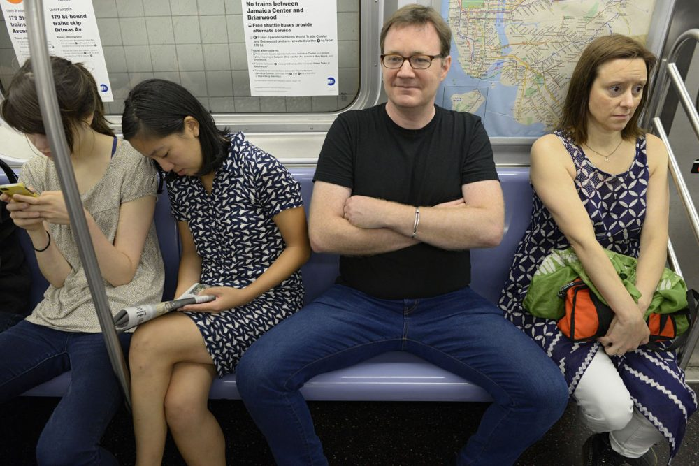 "WNYC employees demonstrate ""manspreading,"" which refers to how men often take up too much space on public transportation. (Richard Yeh/WNYC)"