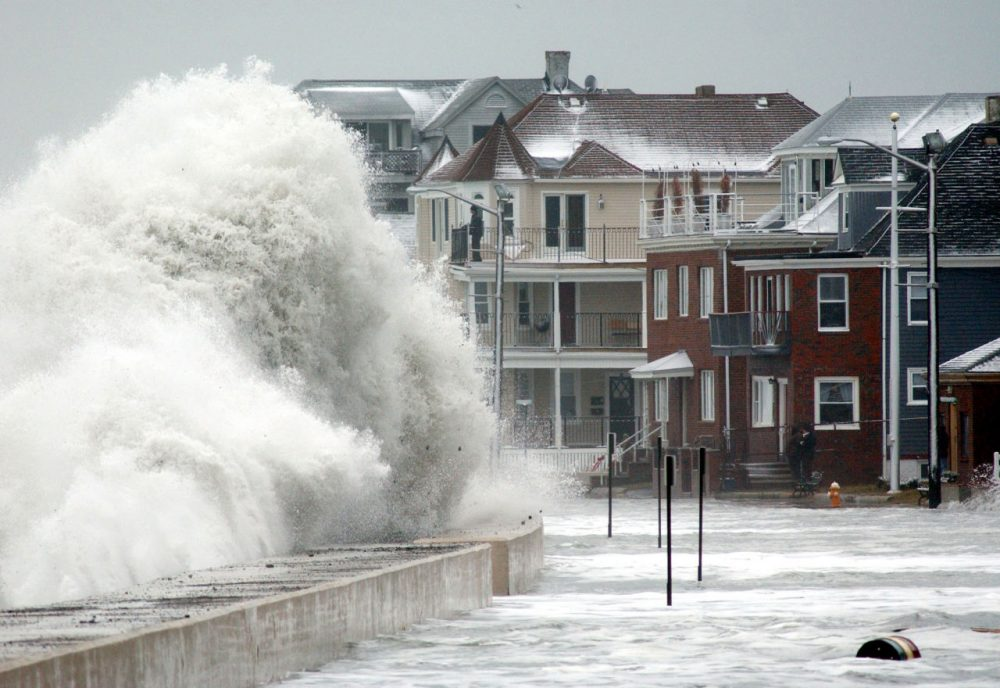 Waves crash over the sea wall in Winthrop, Mass., Saturday, Jan. 4, 2003. Roadways in several coastal communities from Marblehead to Scituate, Mass.,  were closed off and several families were evacuated, as unusually high tidal waves crashed on the shore. (AP Photo/Michael Dwyer)