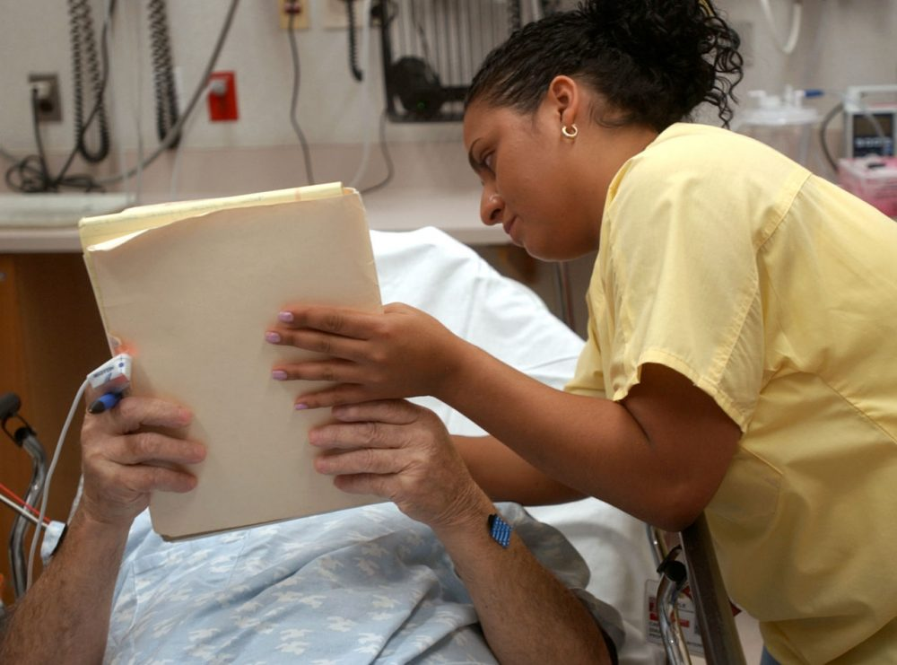 Hospitals take different approaches to support people with low English-speaking ability. In this 2004 photo, medical interpreter Carmen Diaz interprets for Spanish-speaking patient at Temple University Hospital in Philadelphia. (Bradley C. Bower/AP)