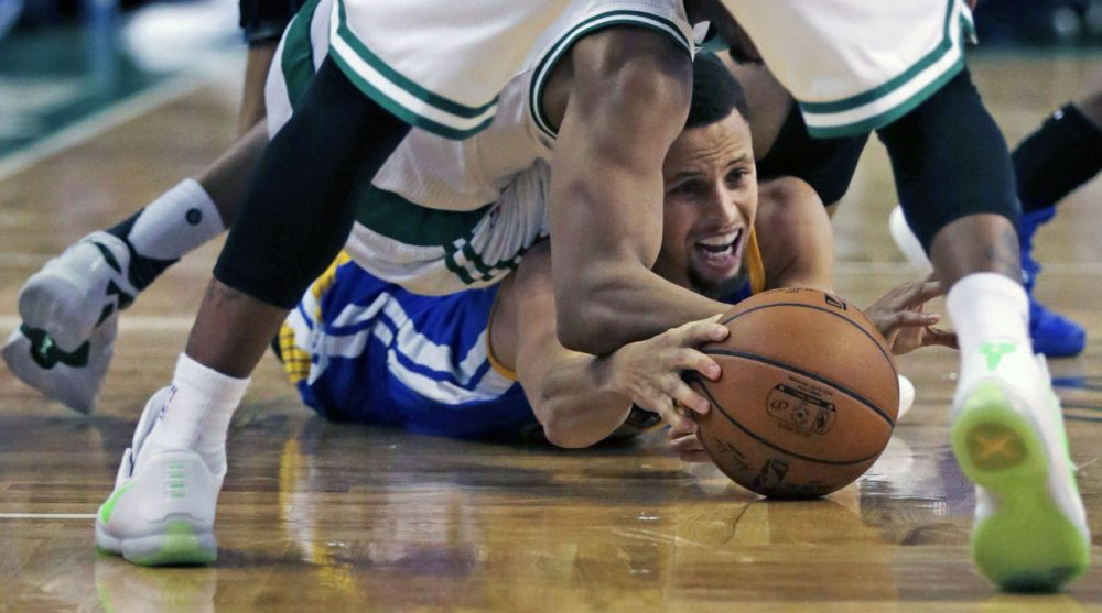 Warriors guard Stephen Curry tries to keep control of the ball as he is surrounded by Celtics during Friday's game in Boston. (Charles Krupa/AP)