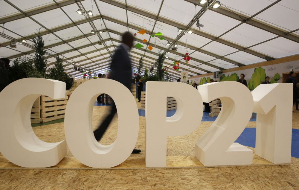 A majority of Massachusetts voters polled put the Paris terror attacks, the presidential election and, yes, the Patriots, higher on their list of interest than the big climate summit happening in France.  Pictured here, a man walks past a display at COP21, the United Nations Climate Change Conference in France. (Christophe Ena/AP)