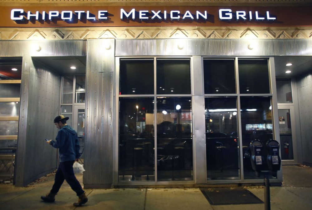 A man walks near a closed Chipotle restaurant on Monday, in the Cleveland Circle neighborhood of Boston. (Steven Senne/AP)