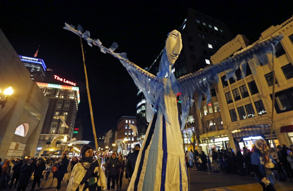 A large puppet makes her way down Boylston Street in the First Night parade during New Year's Eve festivities in Boston's Copley Square, Wednesday, Dec. 31, 2014. (Elise Amendola/AP)
