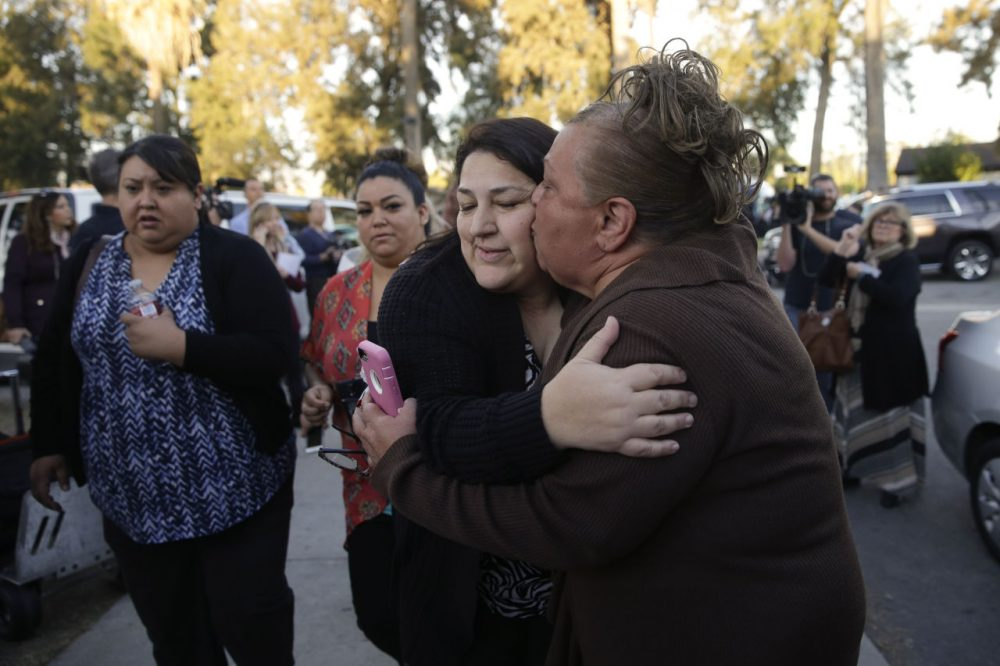 A woman kissed her sister, a survivor of a shooting rampage that killed at least 14 people and wounded more than a dozen others, as they reunited at a community center in San Bernardino Wednesday. (Jae C. Hong/AP)