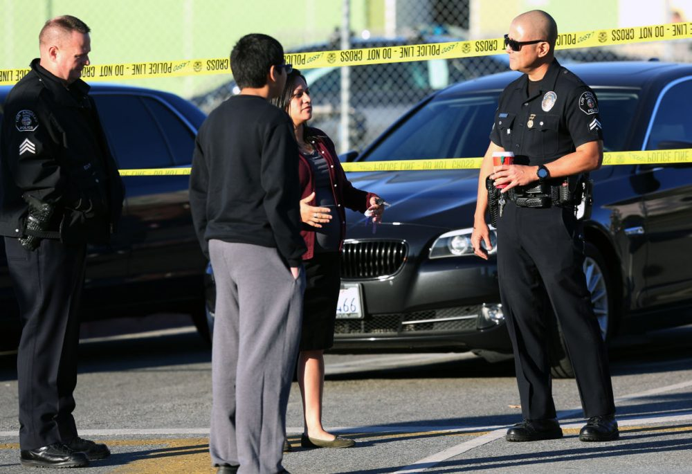Police officers explain to a parent and her son that his school was closed for the day at Edward Roybal High School in Los Angeles, on Tuesday morning, Dec. 15, 2015. (Richard Vogel/AP)