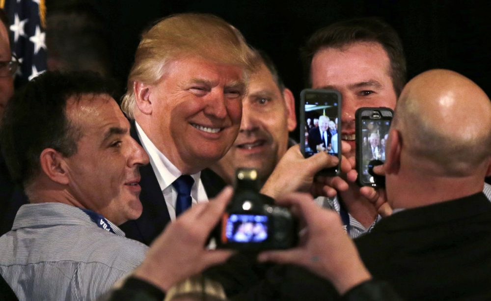 Republican presidential candidate Donald Trump smiles as he has his photograph taken with supporters after being endorsed at a regional police union meeting in Portsmouth, New Hampshire on Thursday. (Charles Krupa/AP)