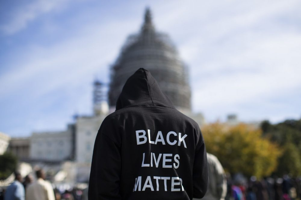 "Neal Blair, of Augusta, Ga., wears a hoodie which reads, ""Black Lives Matter"" as stands on the lawn of the Capitol building during a rally to mark the 20th anniversary of the Million Man March, on Capitol Hill, on Saturday, Oct. 10, 2015, in Washington. Black men from around the nation returned to the capital calling for changes in policing and in black communities. (AP Photo/Evan Vucci)"