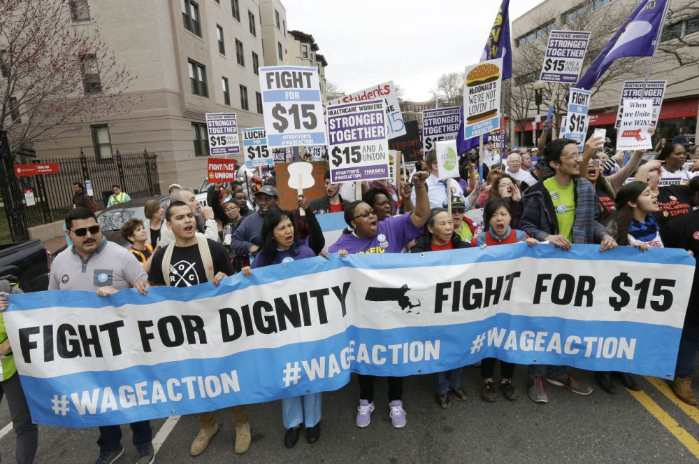 In this April 2015 file photo, protesters chant slogans as they march in Boston. New laws taking effect on Jan. 1, 2016, will raise the minimum wage in several states, including Massachusetts. (Steven Senne/AP)