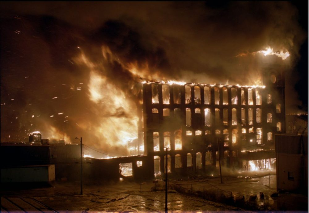 Flaming cinders shoot from one of four mill buildings putting nearby homes in danger as a multi-alarm fire rages at the Malden Mills textile complex in Methuen, Mass. Monday night, Dec. 11, 1995. Thirty-one workers have been reported injured in the fire and explosion, eight critically, with no confirmed deaths. (AP Photo/John Cetrino)