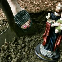 Home seller Diana Grammont of Lexington, Mass., gets ready to dig a hole in her front yard to bury a statue of St. Joseph. The belief that St. Joseph helps homeowners sell their homes traces back to St. Theresa of Avalon, a nun in the 17th century who buried a coin of the saint and prayed to him for help in getting land for monasteries. When the ritual worked, the practice spread. (Elise Amendola/AP)
