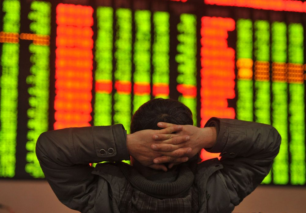 """An investor sits in front of a screen showing stock market movements in a stock firm in Fuyang, east China's Anhui province on January 4, 2016. Trading on the Shanghai and Shenzhen stock exchanges was ended early on January 4 after shares fell seven percent, the first time China's new """"circuit breaker"""" intervened to curb market volatility. (STR/AFP/Getty Images)"""