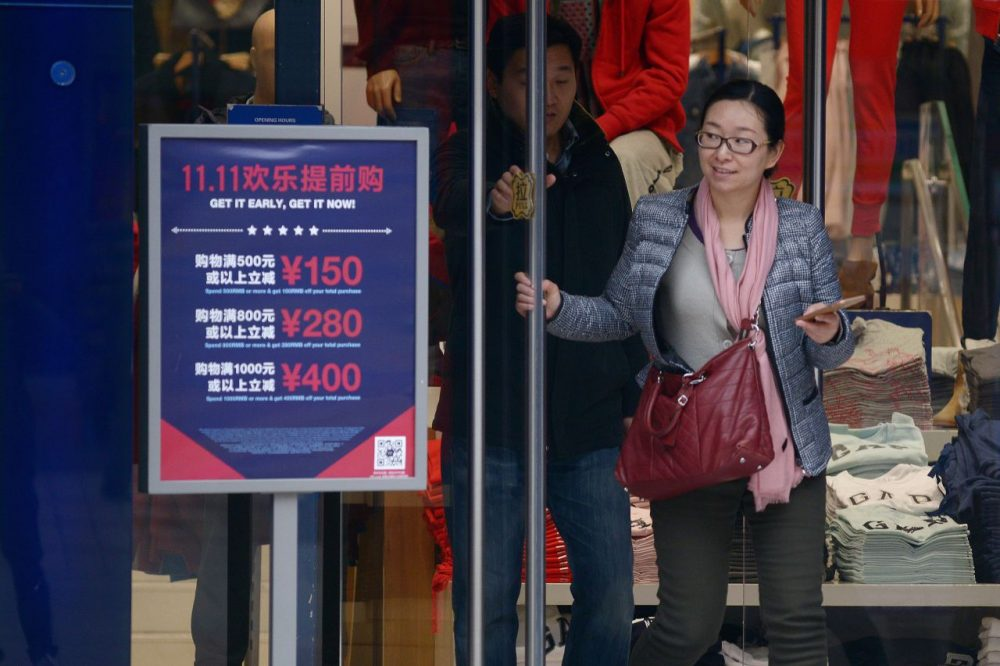 "A woman walks out a shop past a ""Singles Day"" sales promotional board in Beijing on November 11, 2015.  (Wang Zhao/AFP/Getty Images)"