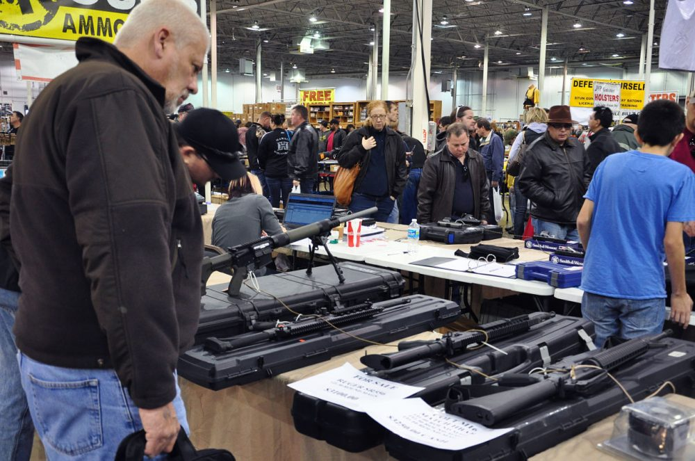 Gun show goers look at various assault-style weapons December 30, 2012 at the Nation's Gun Show in Chantilly, Virginia. Since the Connecticut school shootings, gun sales, particularly assault-style weapons have gone up sharply.  AFP PHOTO/Guillaume MEYER        (Photo credit should read Guillaume Meyer/AFP/Getty Images)