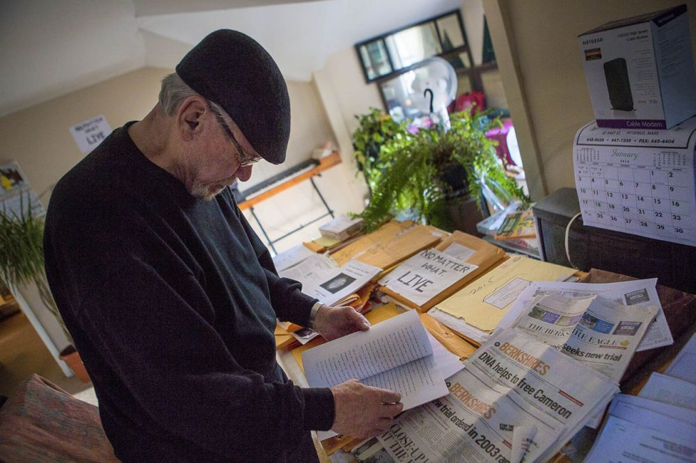 Ronjon Cameron, seen here in late December in his Pittsfield home, pores over DNA and legal documents, as well as old newspapers he has collected, as research for a book he is writing. (Jesse Costa/WBUR)
