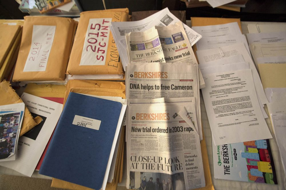 Ronjon Cameron is now free, after the state high court overturned his conviction and prosecutors decided to drop the case. In his Pittsfield home, Cameron's table is full of documents and old newspapers he has collected as research for a book he is writing. (Jesse Costa/WBUR)