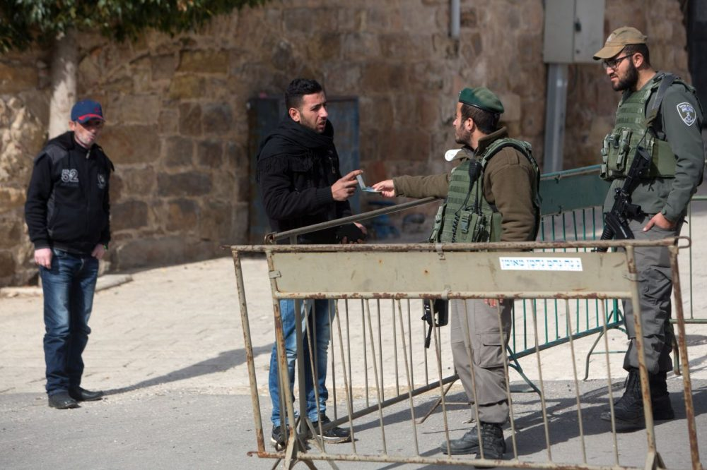 A Palestinian man has his identity checked by Israeli border police patrolling the streets of the West Bank city of Hebron on January 5, 2016. (Menahem Kahana/AFP/Getty Images)
