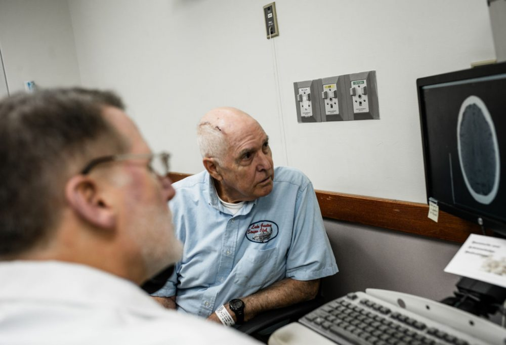 Tom Feild looks at a brain scan with his doctor at Virginia Commonwealth University Medical Center in Richmond, Va. Feild had brain surgery after experiencing a low-grade headache that wouldn't go away and difficulty driving. (Matailong Du for NPR)