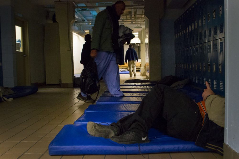Men prepare to sleep on 25-inch-wide mats in the lobby of Boston's Pine Street Inn. (Hadley Green for WBUR)