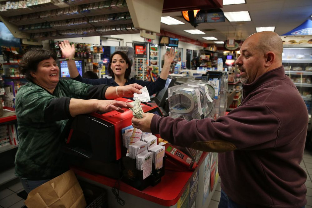 Gale Call (left) and Sherrie Haines (center) sell a Powerball ticket to Mike Nastasi (right) at the BP gas station, January 6, 2015 in Dunkirk, Maryland. (Mark Wilson/Getty Images)