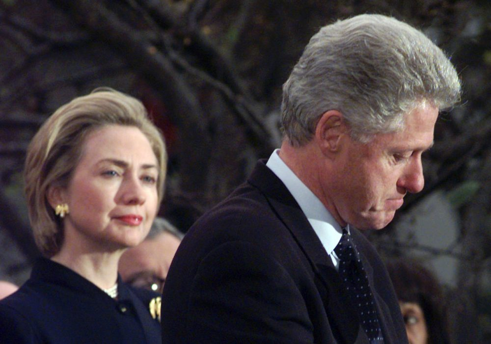 """First lady Hillary Rodham Clinton watches President Clinton pause as he thanks those Democratic members of the House of Representatives who voted against impeachment in this Dec. 19, 1998 photo. Her husband's dalliances with Monica Lewinsky left Americans baffled, and at the same time admiring that Hillary would stand by her husband. """"The most difficult decisions I have made in my life were to stay married to Bill, and to run for the Senate from New York,"""" she said. She decided she wanted the marriage to last, if that was possible. (Susan Walsh/AP)"""