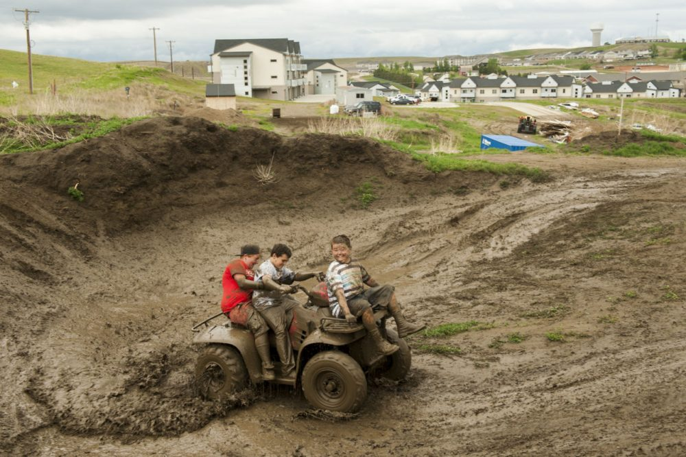 Children ride an ATV through a muddy construction area at the edge of a housing development  in Watford City, North Dakota, one of many built during the oil boom. (Andrew Cullen)