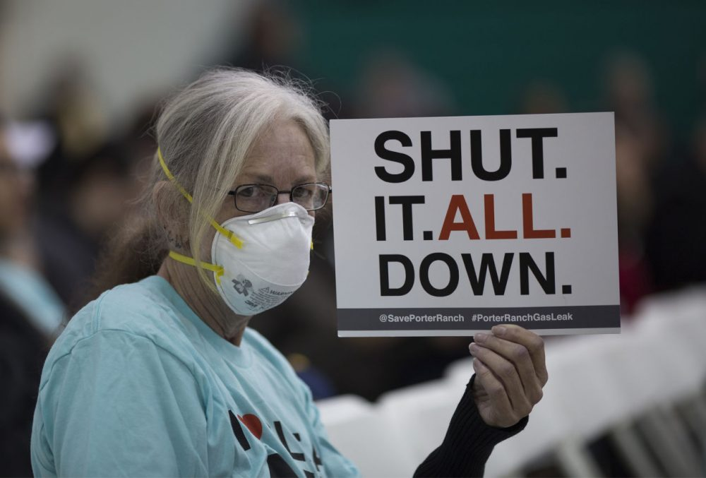 A woman holds a sign while attending a public hearing before the South Coast Air Quality Management District (AQMD) regarding a proposed stipulated abatement order to stop a nearby massive natural gas leak, on January 16, 2016 in Granada Hills, near Porter Ranch, California. More than 80,000 metric tons of methane gas have spewed from the Aliso Canyon natural gas storage facility since October 23, causing thousands of Porter Ranch residents to leave their homes, and the closures of two schools where students are being bussed to campuses farther away from the gas. State officials are now concerned that a seventh attempt to plug the well may have increased the chance of a blowout, which would greatly increase the release of gas as well as the risk of a massive well fire if ignited by a spark. The Southern California Gas Company (SoCalGas) hopes to repair the leak by sometime in March.  (David McNew/Getty Images)