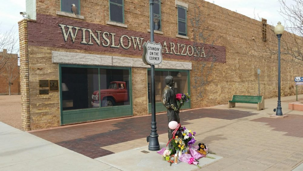 "The corner in Winslow, Arizona, made famous by the 1972 Eagles' song ""Take it Easy,"" is pictured on Jan. 19, 2016. Fans are leaving flowers, hand-written notes and candles at the site to celebrate the life of Eagles band member Glenn Frey, who died Monday at 67. (Tom McCauley via AP)"