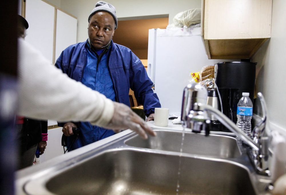 A handyman explains a new water filter to Terrence Tyler at his residence in Shiloh Commons, January 21, 2016 in Flint, Michigan. The city's water supply had been contaminated by lead after a switch from Lake Huron to the Flint river as a source in April, 2014. At a local fire station, residents were provided with water testing jugs, filters and clean water brought in by the National Guard. Residents also brought in water samples from their homes which would be sent out for lead testing. (Sarah Rice/Getty Images)