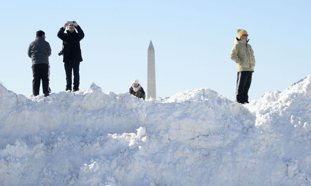 """People stand on top of a pile of snow on January 24, 2016 in Washington, D.C. Millions of people in the eastern United States started digging out Sunday from a huge blizzard that brought New York and Washington to a standstill, but the travel woes were far from over. The storm -- dubbed """"Snowzilla"""" -- killed at least 18 people after it walloped several states over 36 hours on Friday and Saturday, affecting an estimated 85 million residents who were told to stay off the roads and hunker down in doors for their own safety. (Olivier Douliery/AFP/Getty Images)"""