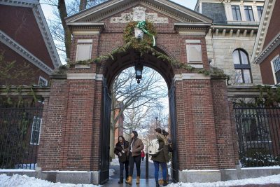 Students walking in and out of one of the gates of Harvard Yard at Harvard University. (Jesse Costa/WBUR)