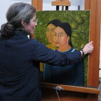 """MFA Conservator of Paintings Rhona MacBeth places Frida Kahlo's """"Dos Mujeres (Salvadora y Herminia) (1928)"""" on an easel for display. It was the first painting Kahlo ever sold. (Andrea Shea/WBUR)"""