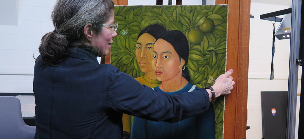 "MFA Conservator of Paintings Rhona MacBeth places Frida Kahlo's ""Dos Mujeres (Salvadora y Herminia) (1928)"" on an easel for display. It was the first painting Kahlo ever sold. (Andrea Shea/WBUR)"