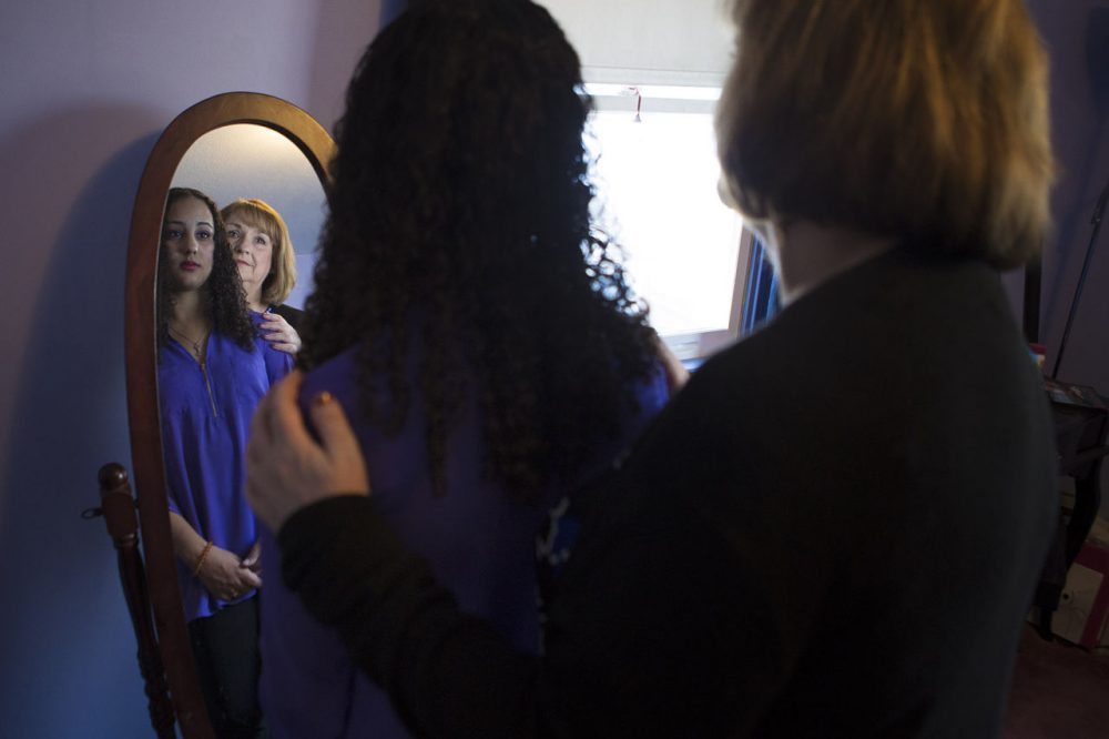 Sydney and her mother Lori looking into the mirror where Sydney experienced her first symptoms of schizophrenia. (Jesse Costa/WBUR)