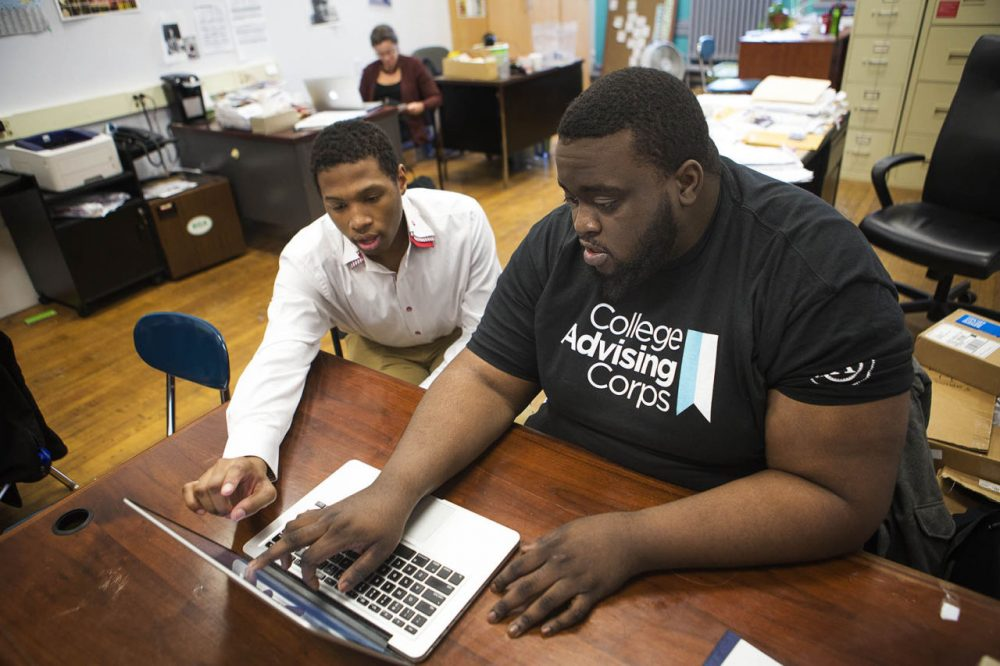 College Advising Corps aims to increase the number of low-income students who apply to college. The nonprofit currently has advisers in 24 Boston high schools. Pictured here, senior Josue Jean-Pierre, left,  and Rudy Luders, with College Advising Corps, review college application information at the Green Academy in Brighton. (Jesse Costa/WBUR)