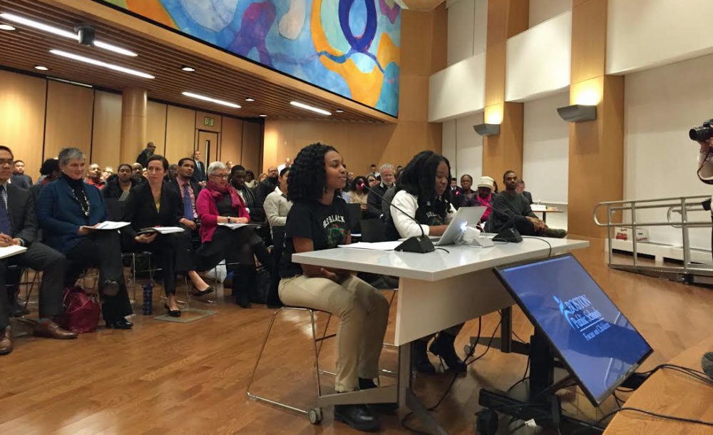 Boston Latin students Kylie Webster-Cazeau and Meggie Noel speak before the Boston School Committee on Wednesday about what they say is a racially hostile environment at their school. (Delores Handy/WBUR)