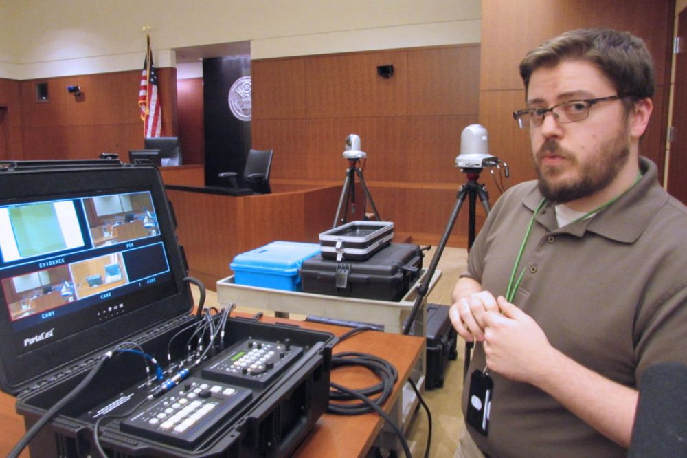Courtroom technology administrator Jeremy Sites explains the camera setup in U.S. District Court. (Amy Radil/KUOW)