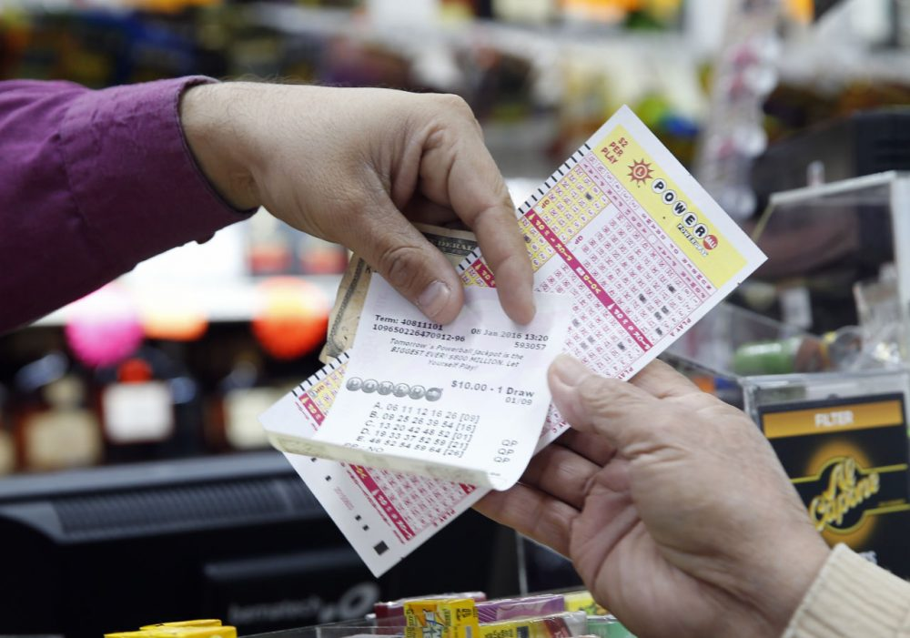 Money and Powerball tickets change hands at Pine Liquors in Fort Washington, Md., Friday, Jan. 8, 2016, for the upcoming Powerball drawing.  (Alex Brandon/AP)