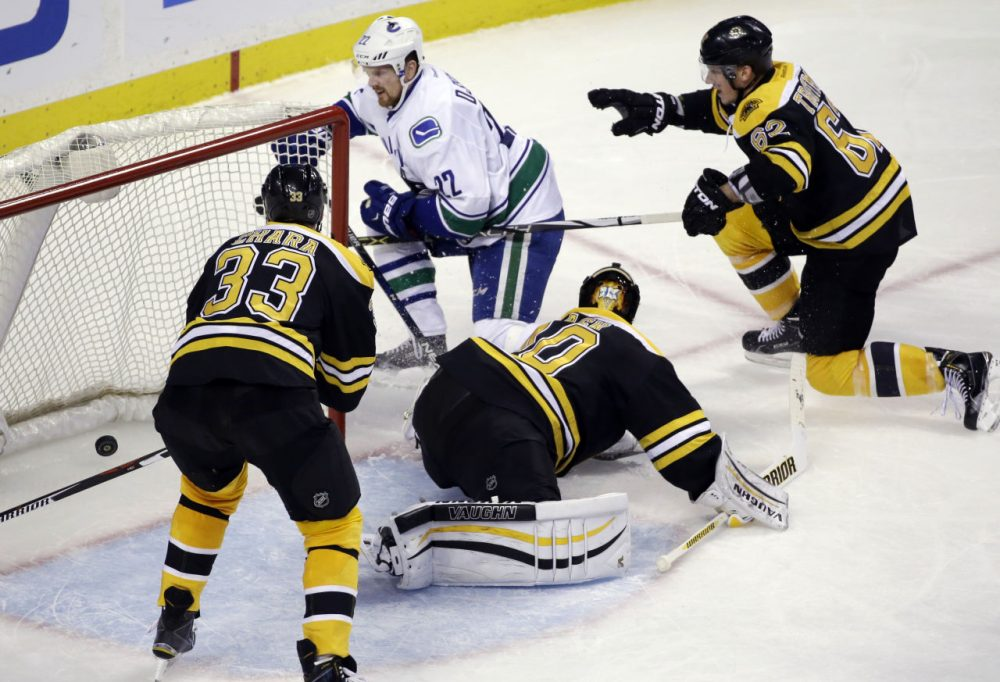 Canucks left wing Daniel Sedin (22) scores against Bruins goalie Tuukka Rask (40) as Bruins defensemen Zdeno Chara (33) and Zach Trotman (62) try to prevent the goal during Thursday's game in Boston. (Elise Amendola/AP)