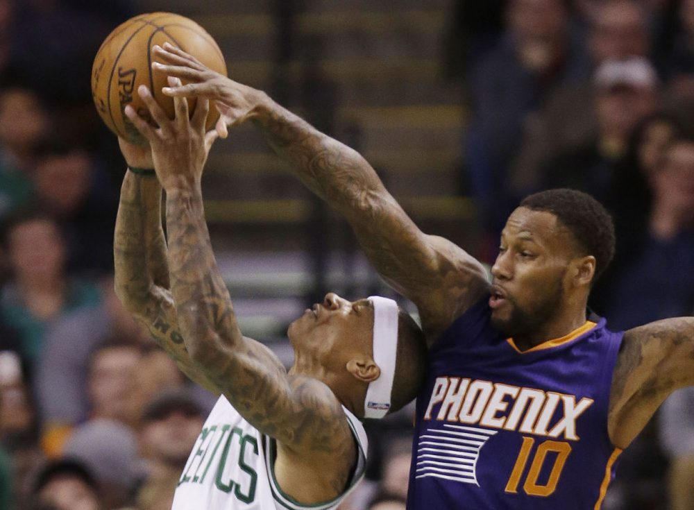 Boston Celtics guard Isaiah Thomas (4) shoots past the attempted block by Phoenix Suns guard Sonny Weems (10) during Friday's game in Boston. (Stephan Savoia/AP)