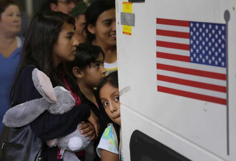 In this July 2015 file photo, immigrants from El Salvador and Guatemala who entered the country illegally board a bus after they were released from a family detention center in Texas. The Department of Homeland Security has recently begun raids to deport people who have illegally entered the U.S. within the last two years and have been issued final orders of removal. (Eric Gay/AP)
