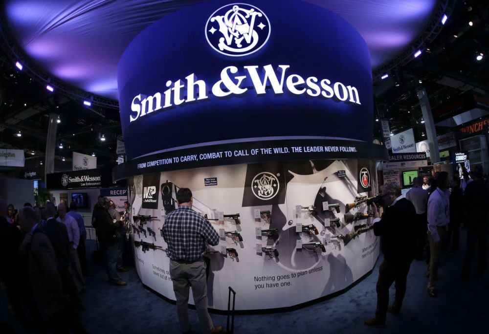 In this 2014 file photo, Las Vegas trade show attendees examine handguns and rifles in the Smith & Wesson display booth. The Springfield firearms maker's shares jumped Monday. (Julie Jacobson/AP)