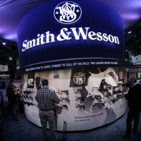 In this 2014 file photo, Las Vegas trade show attendees examine handguns and rifles in the Smith & Wesson display booth. (Julie Jacobson/AP)