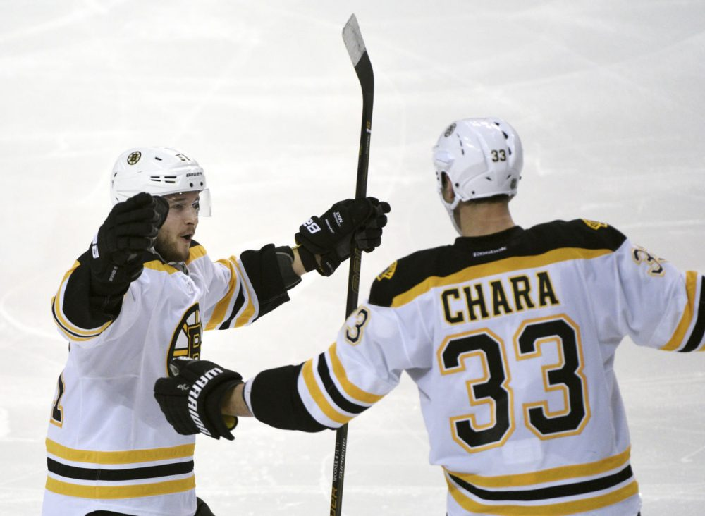 Boston Bruins center Ryan Spooner (51) celebrates with Zdeno Chara (33) after Chara scored during a game against the Buffalo Sabres on Friday. (Gary Wiepert/AP)
