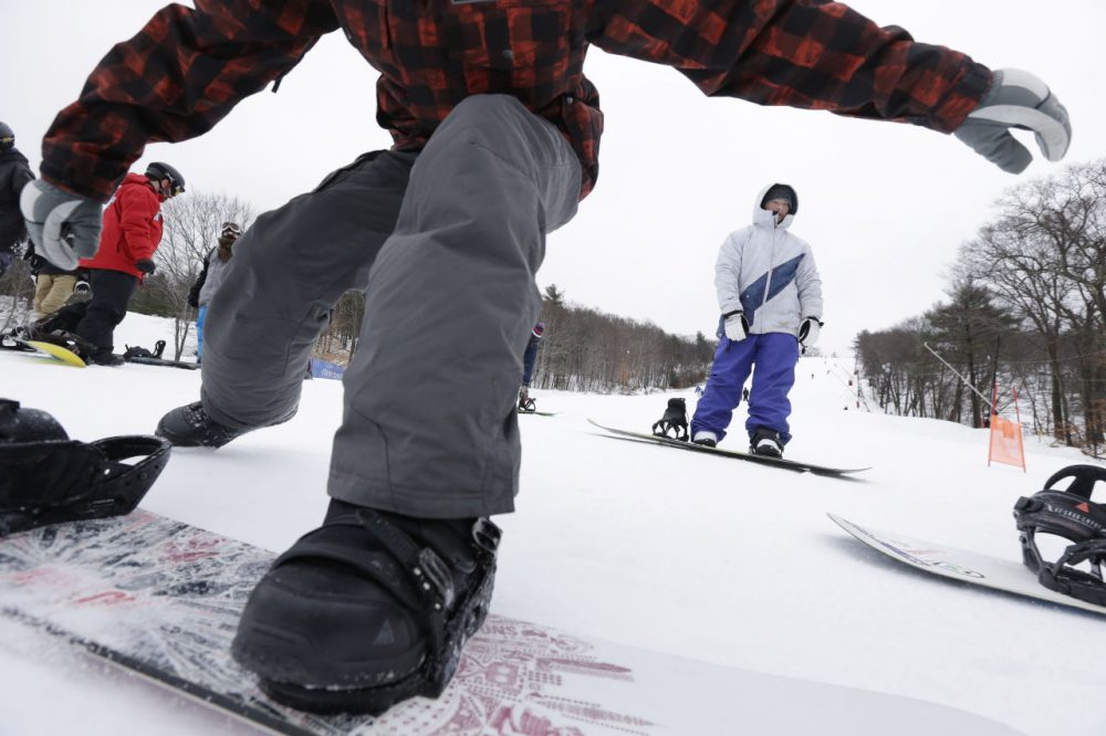In this 2013 file photo, snowboarders traverse make their way toward a chairlift at Blue Hills Ski Area in Canton. (Steven Senne/AP)